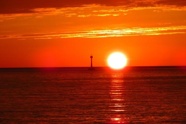 海と灯標を照らす夕日